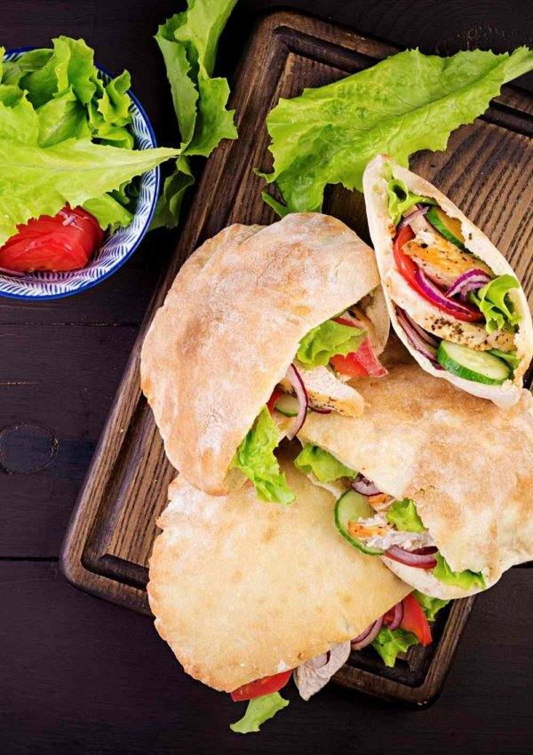 4 GREEK CHICKEN PITAS WITH LETTUCE, TOMATO AND RED ONION ON A CUTTING BOARD