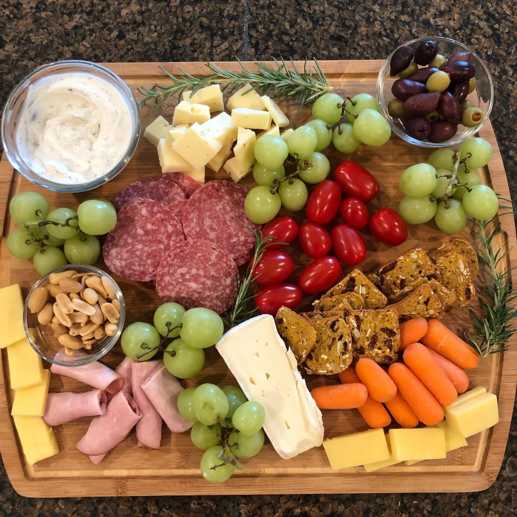 A VARIETY OF MEAT CHEESE AND VEGETABLES ON A WOODEN CUTTING CHARCUTERIE BOARD