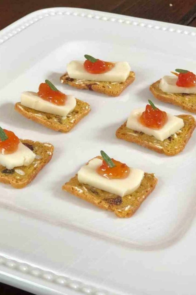 BRIE AND CRACKERS ON A WHITE PLATE TOPPED WITH TOMATO JAM