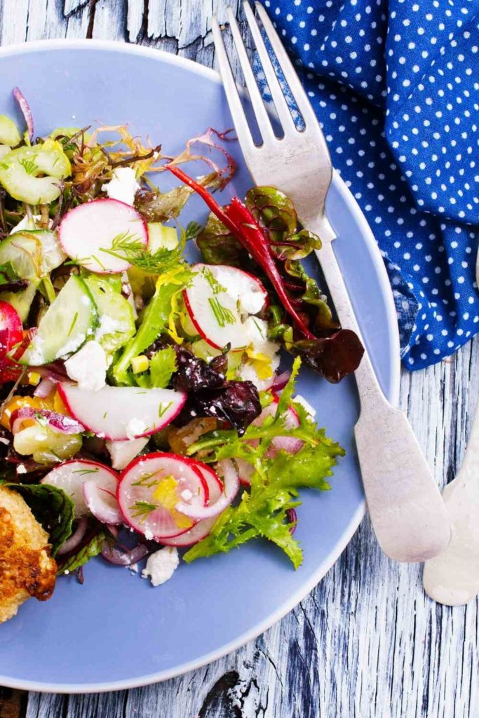 SALAD ON A PLATE WITH FORK AND BLUE NAPKIN