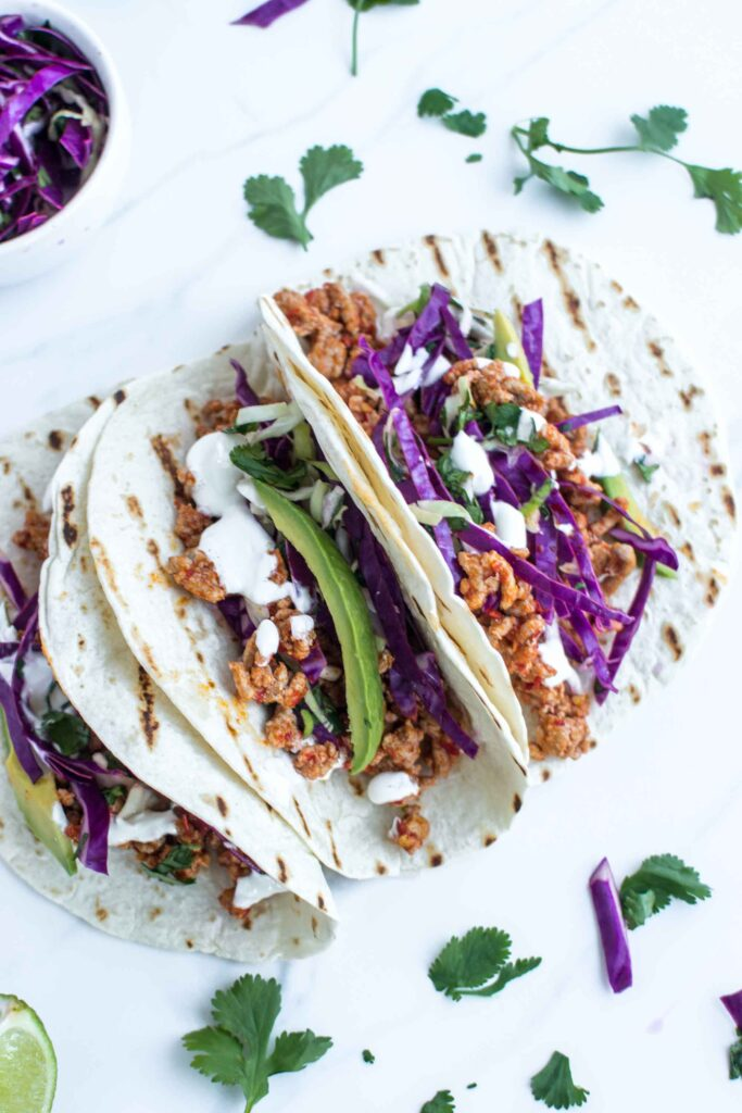 3 tacos on a plate with cabbage and avocado