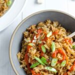 fried rice in bowl with sriracha and scallions