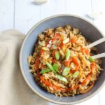 fried rice in a bowl with sriracha sauce and scallions