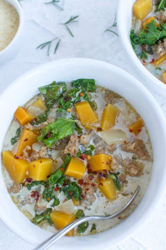 butternut squash soup in a bowl with kale and parmesan cheese