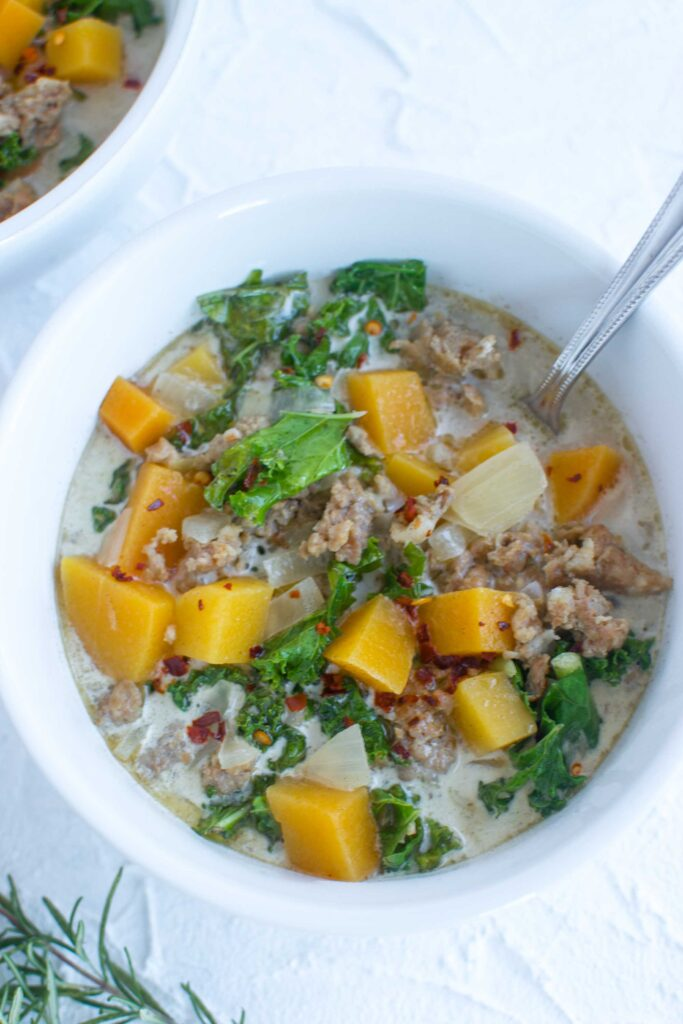 Butternut Squash Soup in a bowl with red pepper flakes and a spoon