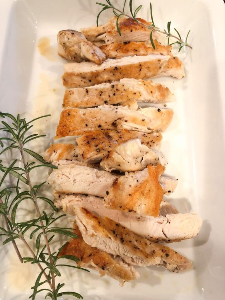 Cooked chicken on a white plate with rosemary