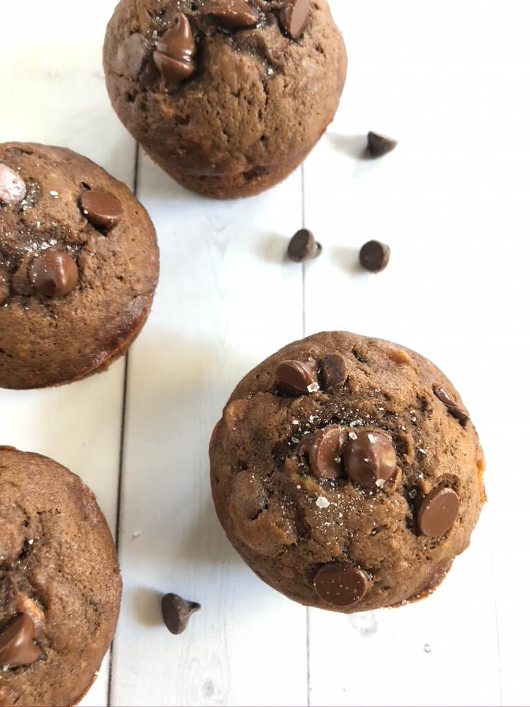 Chocolate chips banana muffins on a table with chocolate chips sprinkled around.