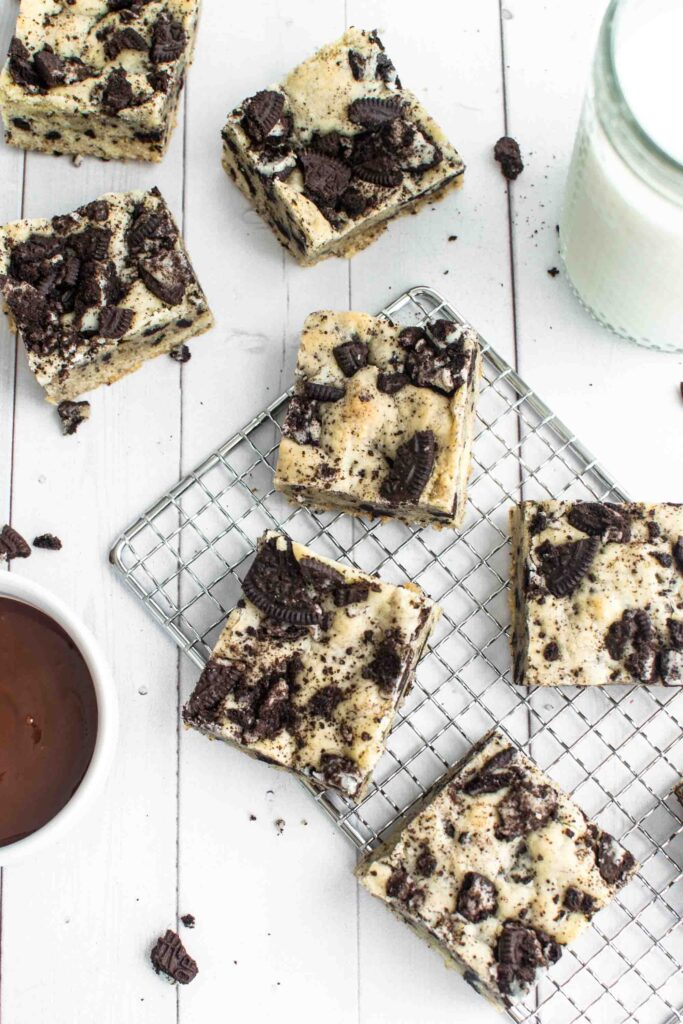 Oreo blondies on a cooling rack with a glass of milk and a little chocolate