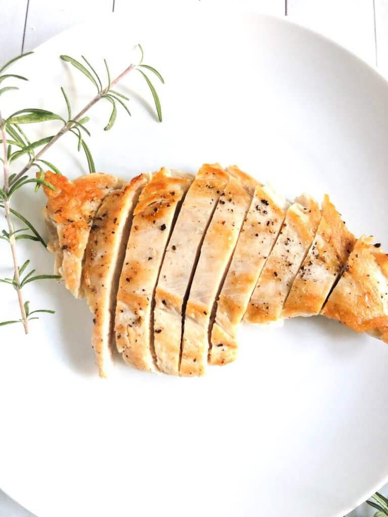 Cooked chicken breast on a white plate with rosemary.