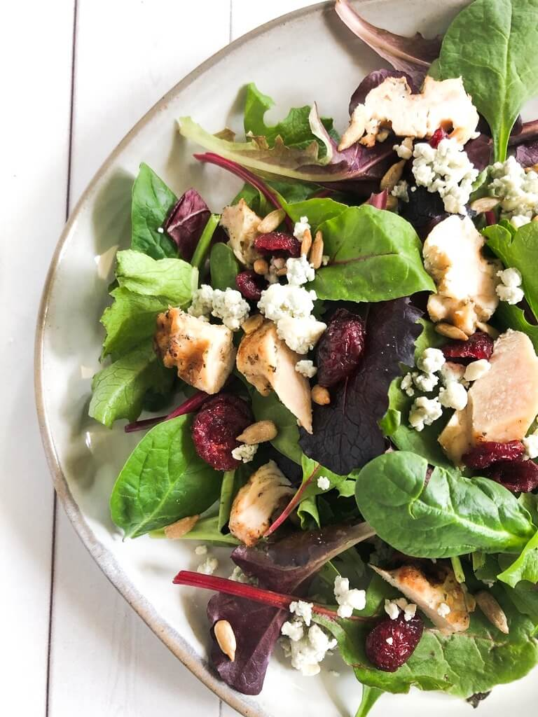 Salad with mixed greens, blue cheese and cranberries on a plate.