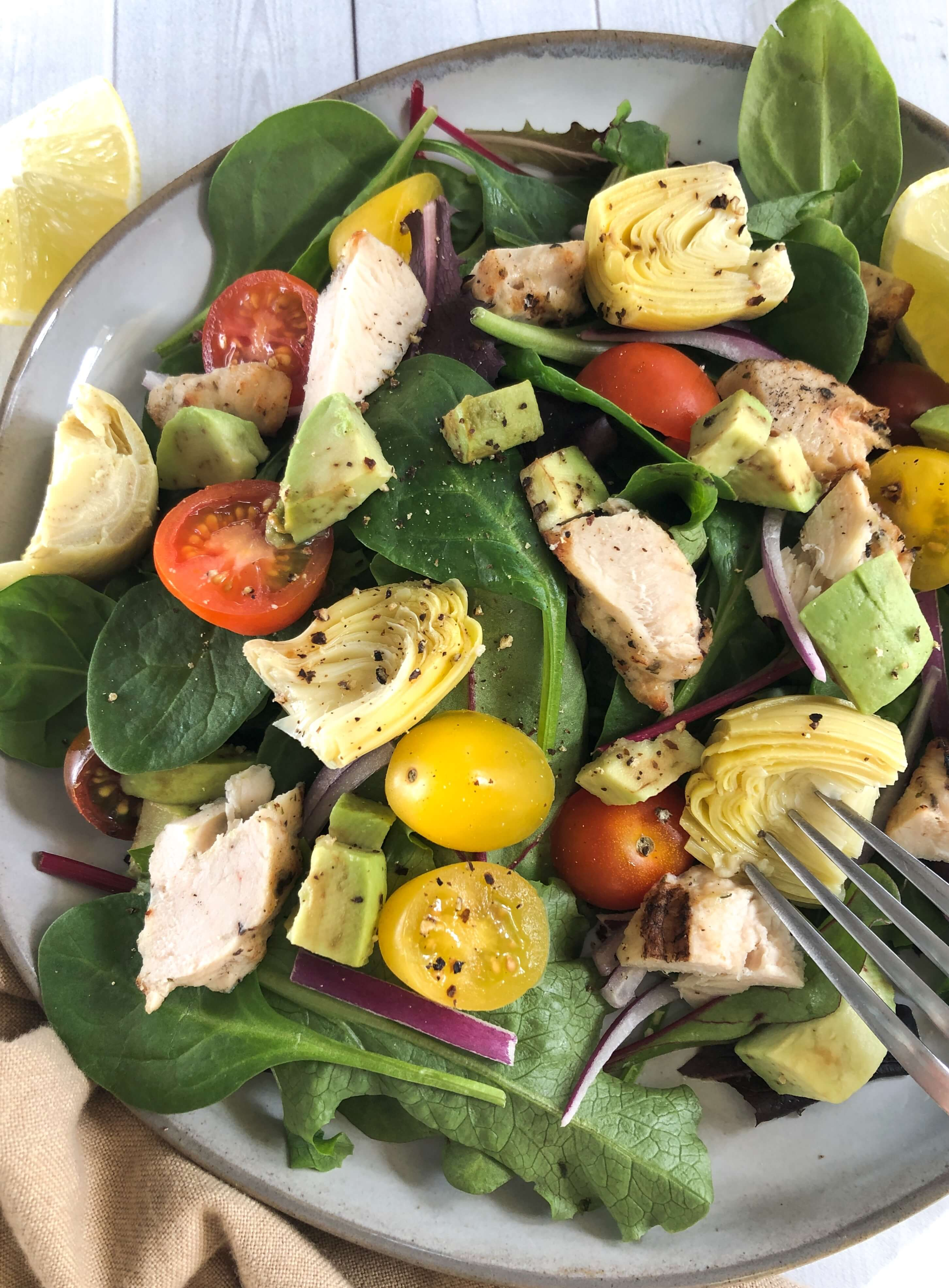 Salad with mixed greens, chicken artichokes and tomatoes on a plate with lemon.