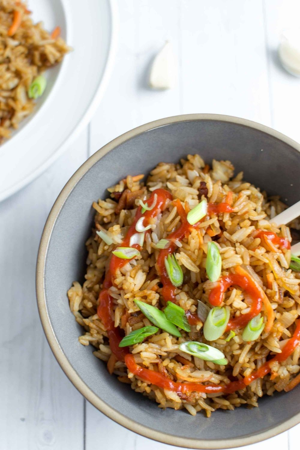 fried rice in a bowl with srirachs and scallions