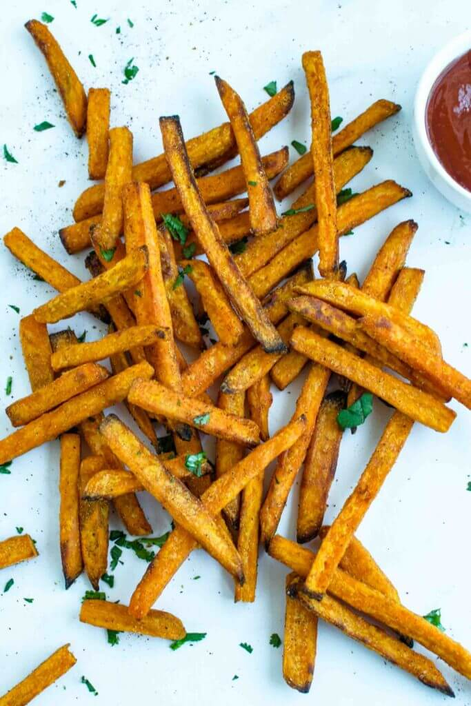Frozen sweet potatoes cooked in the air fryer with ketchup on a plate