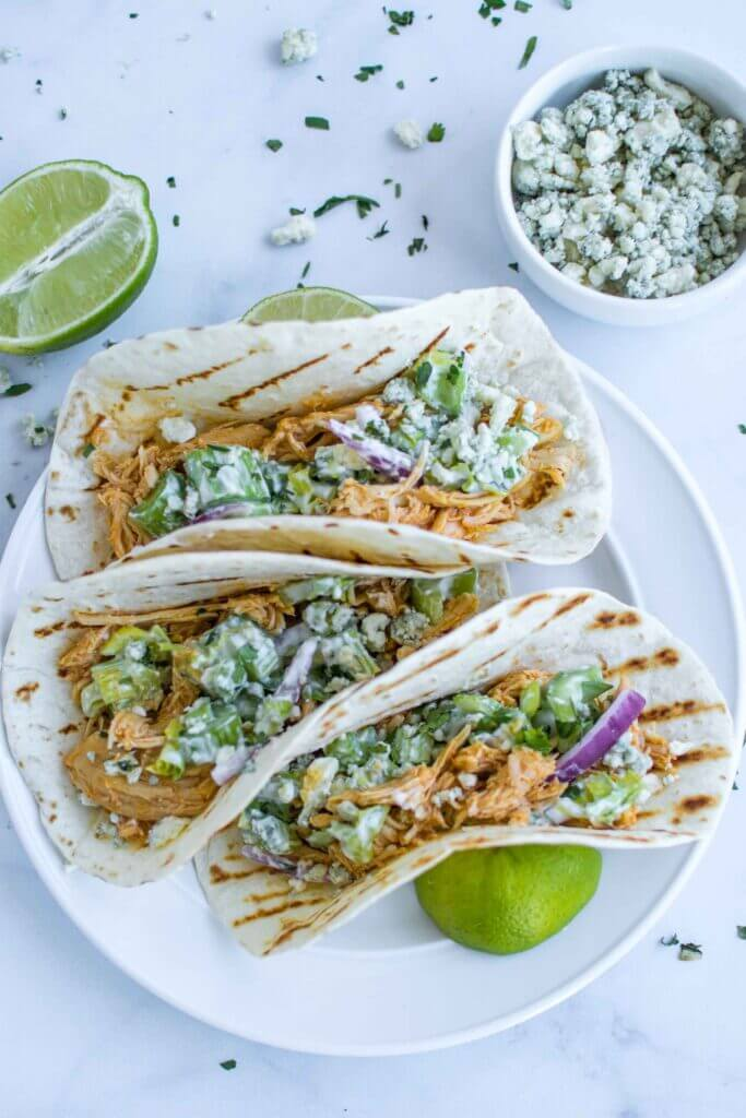Three buffalo chicken tacos on a plate with blue cheese and lime