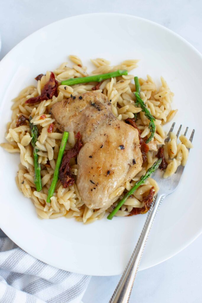 Creamy chicken with sun dried tomatoes and asparagus on a plate with a fork