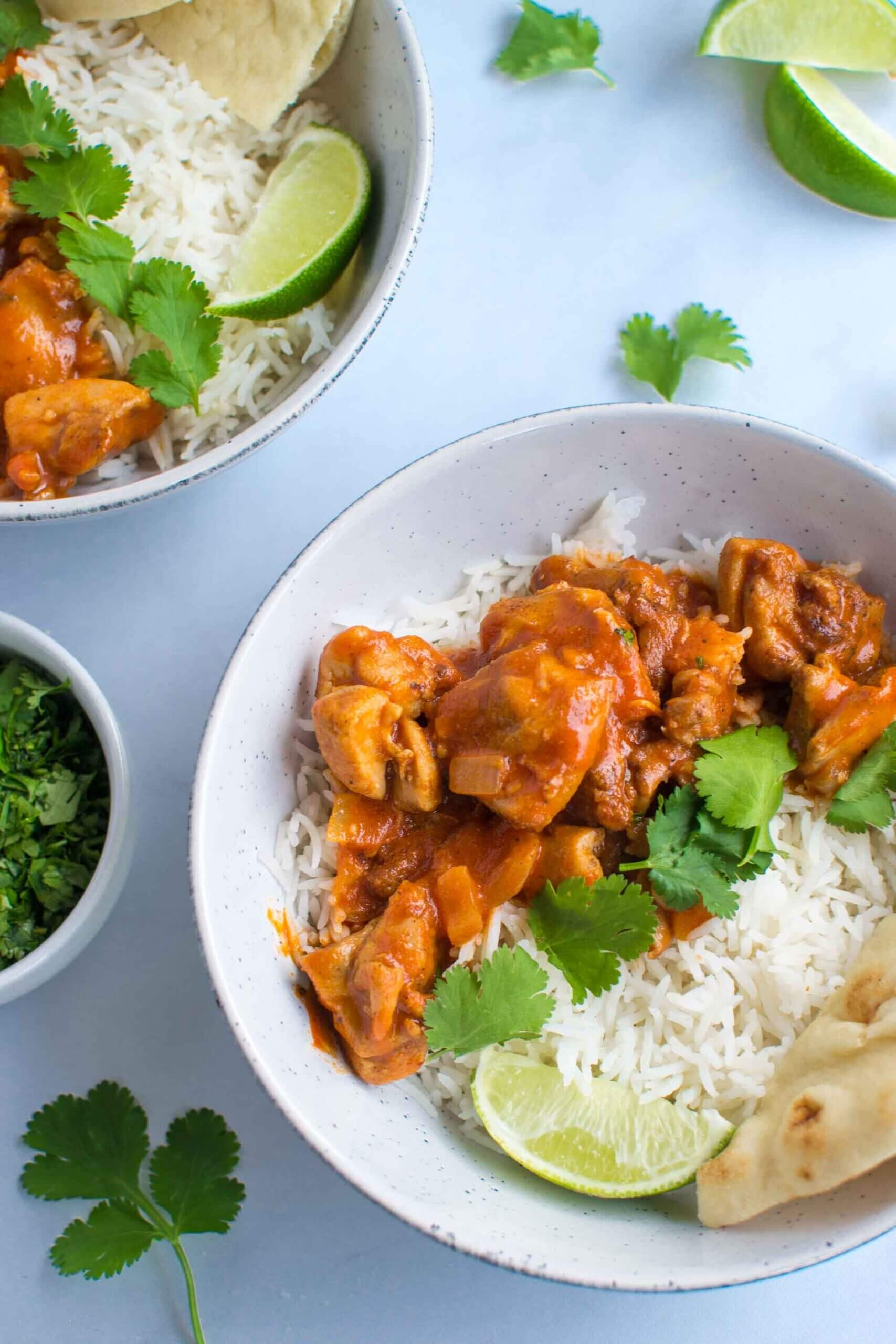 Coconut chicken curry in a bowl with rice, cilantro and naan bread