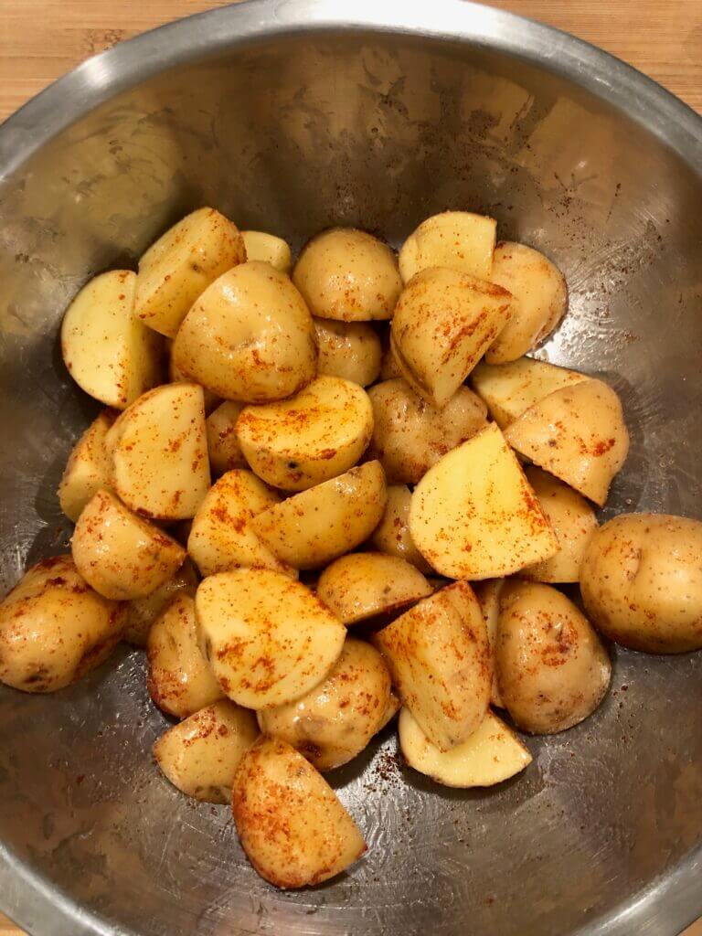 Uncooked potatoes, seasoned in a bowl