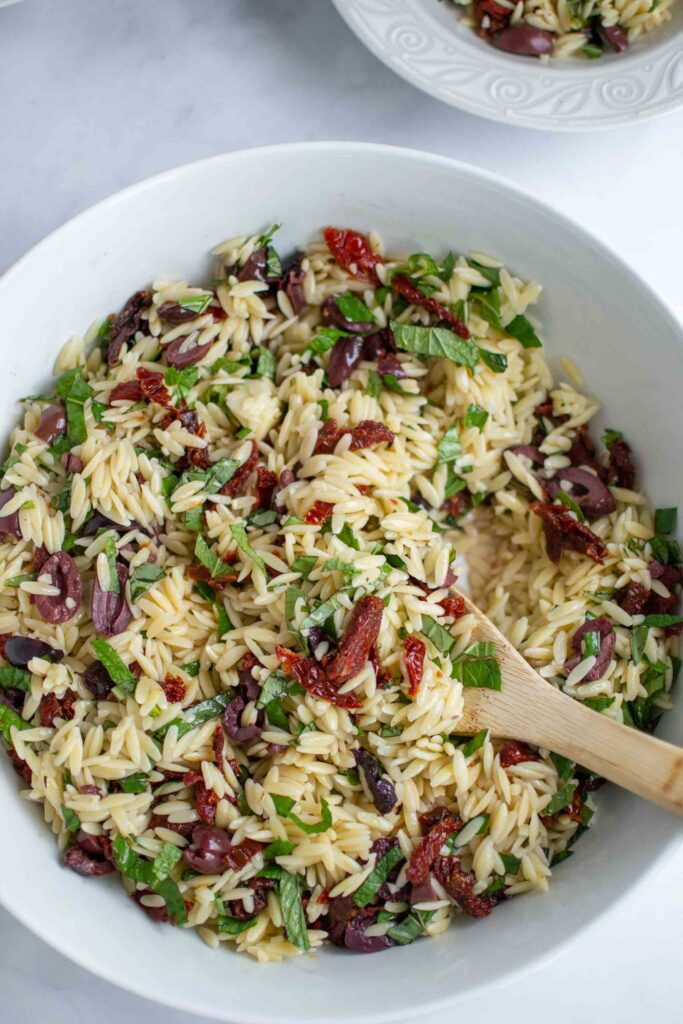 Perfect Orzo Salad in a bowl with fresh herbs, olives and sun dried tomatoes.