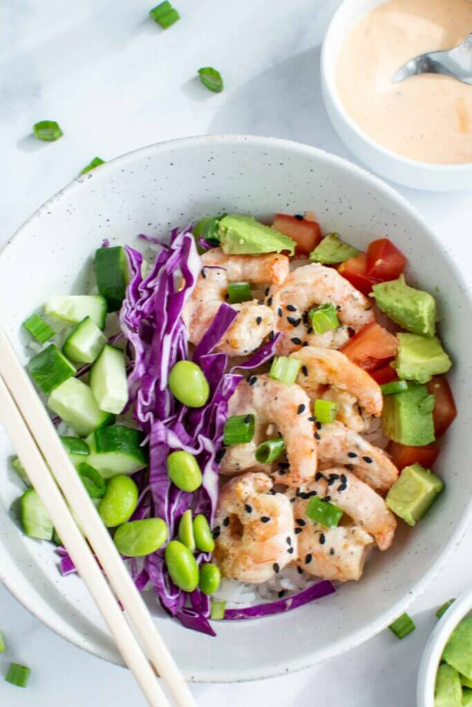 Spicy shrimp poke bowl with cabbage, edamame, avocado, tomato and cucumber. Topped with sriracha mayo.