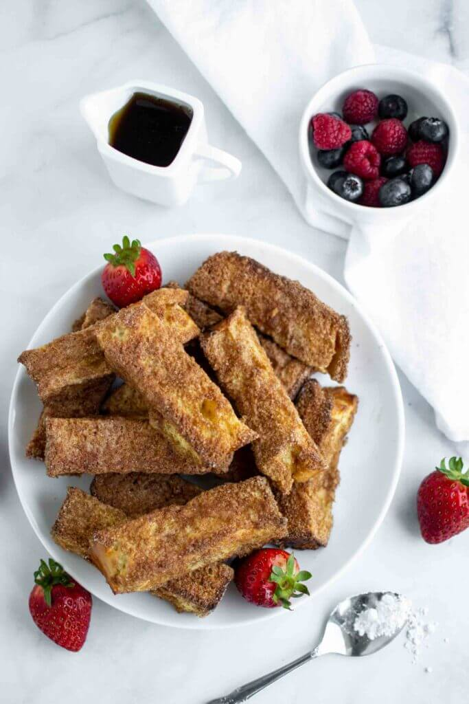 Air Fryer French Toast Sticks on a plate with strawberries and powdered sugar.