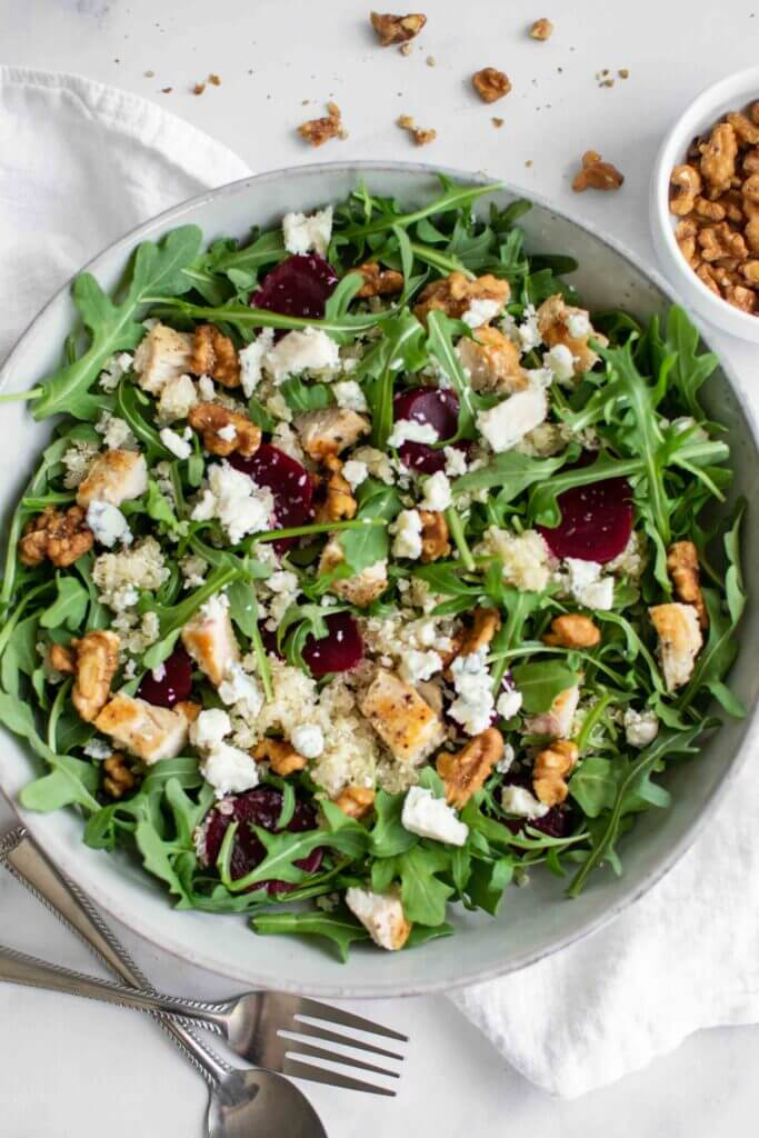Quinoa and arugula salad in a bowl with beets, chicken and gorgonzola cheese