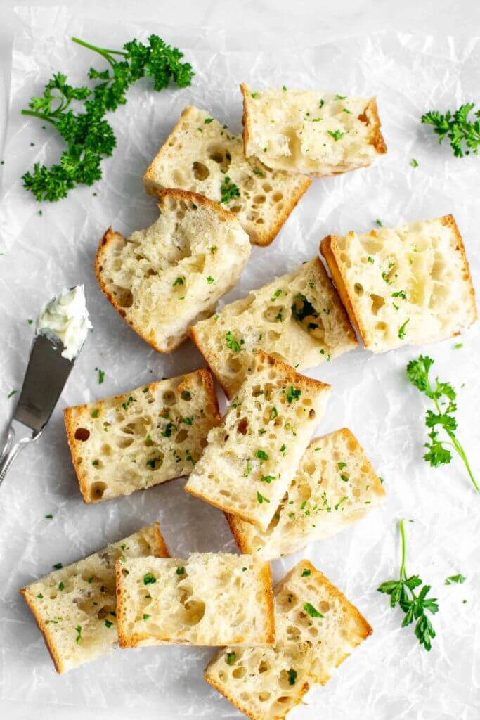 Pieces of air fryer garlic bread on a cutting board with parsley and a butter knife.