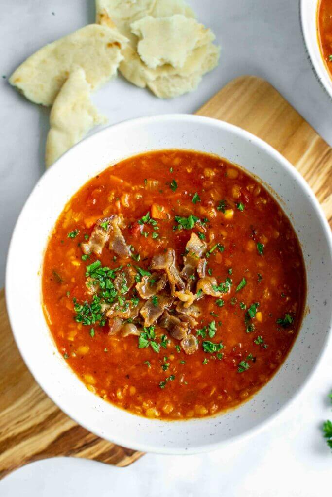 Two bowls of Instant Pot Red Lentil Soup with parsley garnished with bacon