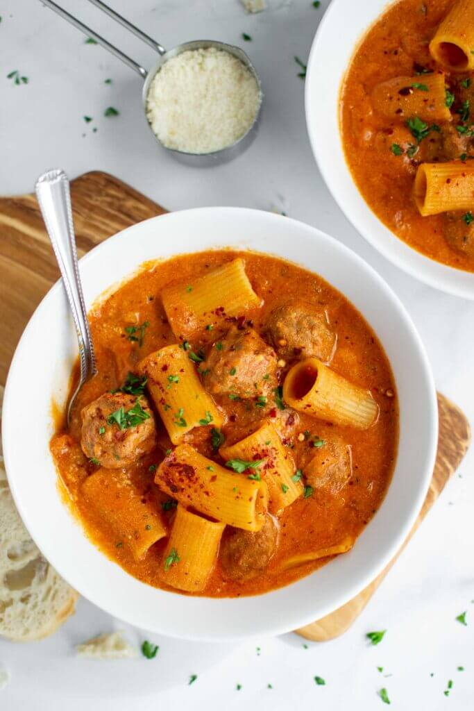 Two bowls of Rigatoni Meatball Soup in a bowl with parsley and french bread.