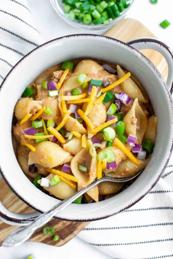 Creamy Crockpot Taco Pasta in a bowl topped with red onion, cheese and scallions.