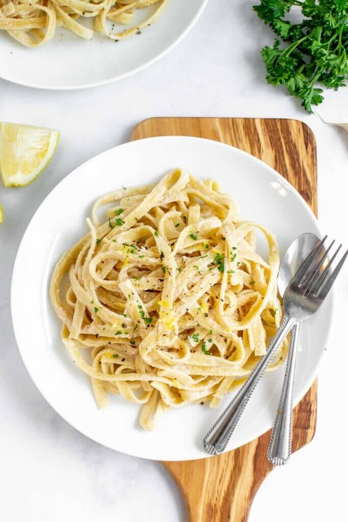 Creamy Lemon and Garlic Tahini Pasta  on a plate with lemon and parsley.