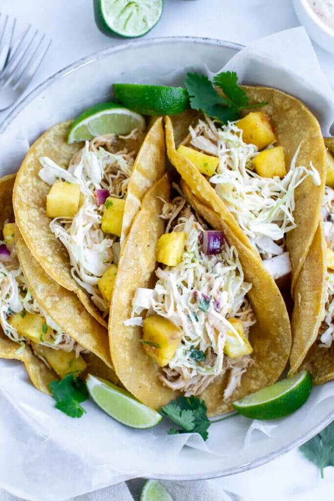 Four Crockpot Hawaiian Chicken Tacos on a plate with lime
