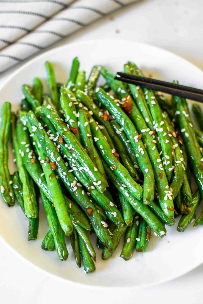 Chinese Style Air Fryer Green Beans on a plate with sesame seeds and chop sticks.