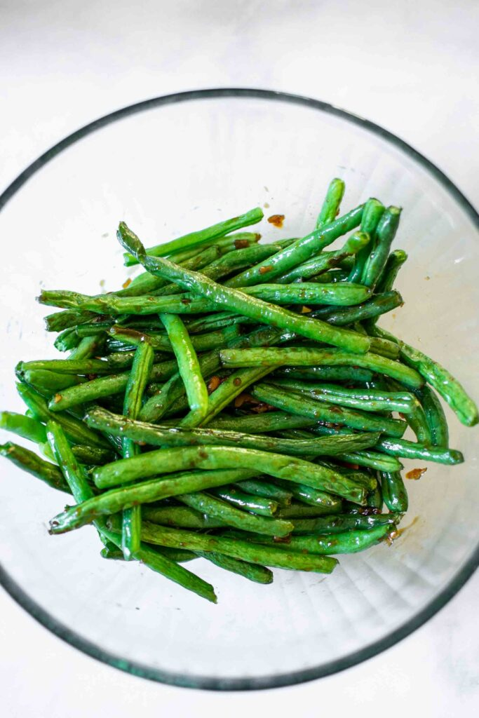 Chinese Style Air Fryer Green Beans in a bowl tossed with the sauce.