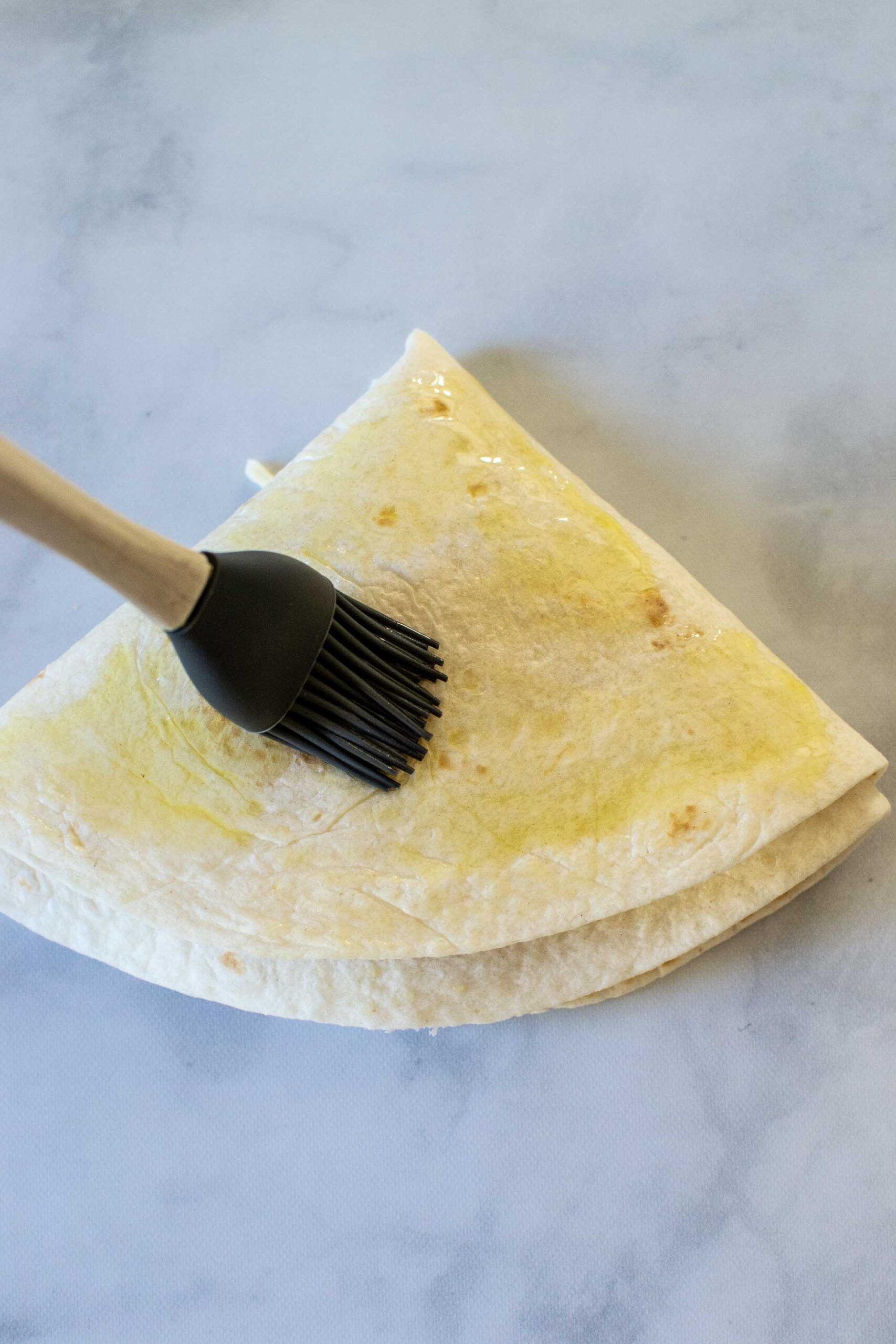 """Step 4 of making a Pizza Tortilla Wrap or Pizza """"Tortilla Trend."""" Brush with oil."""