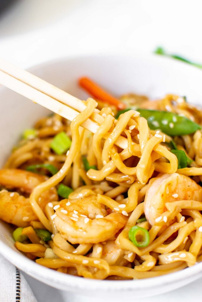 Yaki udon with shrimp in a bowl. Close up of noodles on chop sticks.