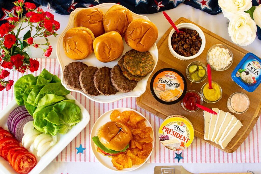 Burger bar set up with burgers, buns and condiments and 4th of July decorations.