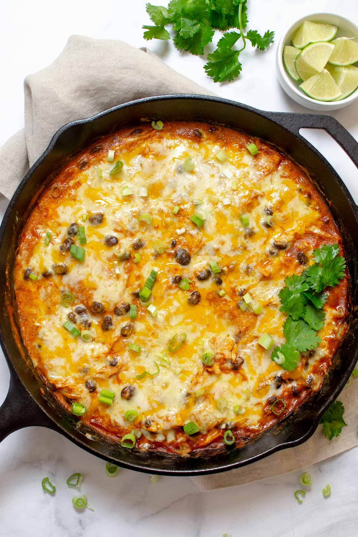 Chicken enchilada skillet on a table garnished with cilantro and lime wedges.