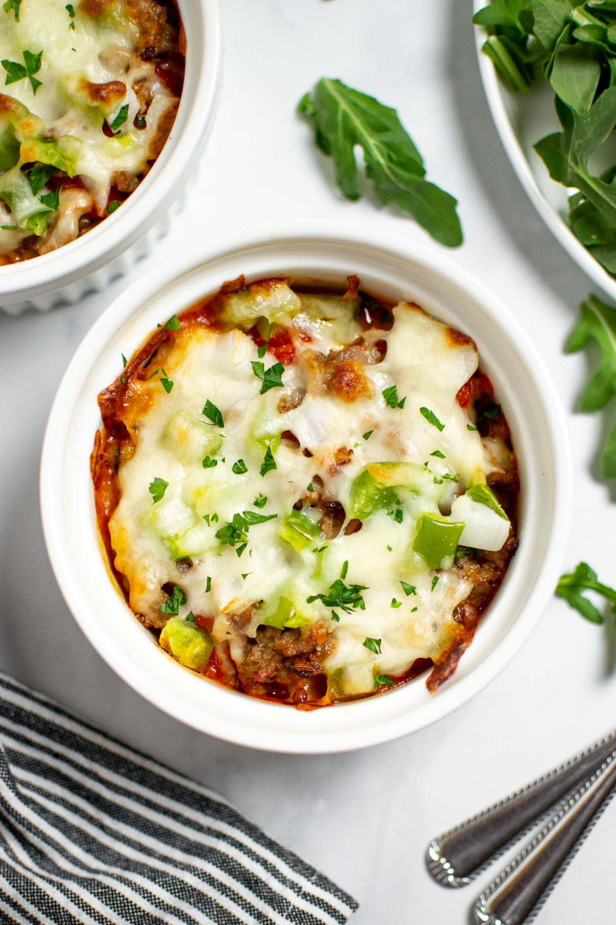 Pizza Bowl with cheese, green pepper, sausage and onions in a white ramekin