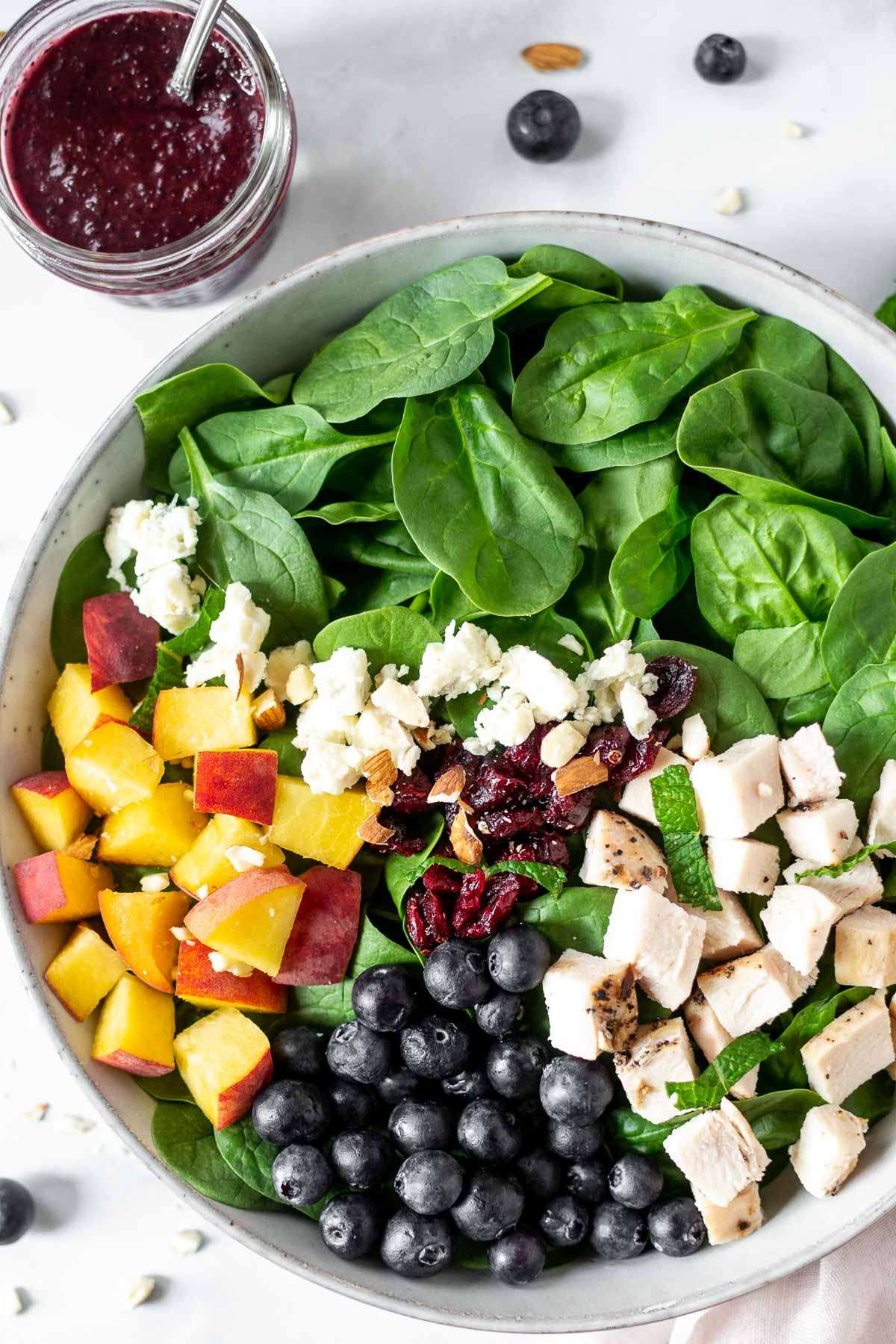 Blueberry and peach salad with the blueberry dressing in a jar.