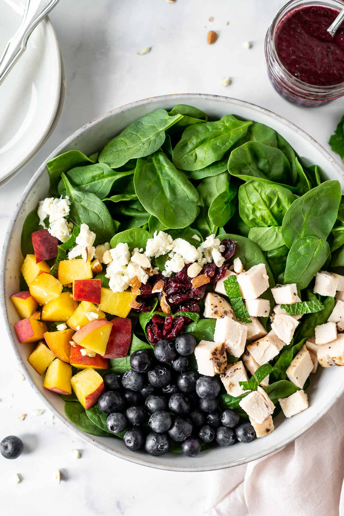 Peach and blueberry salad in a bowl with dressing and salad plates.