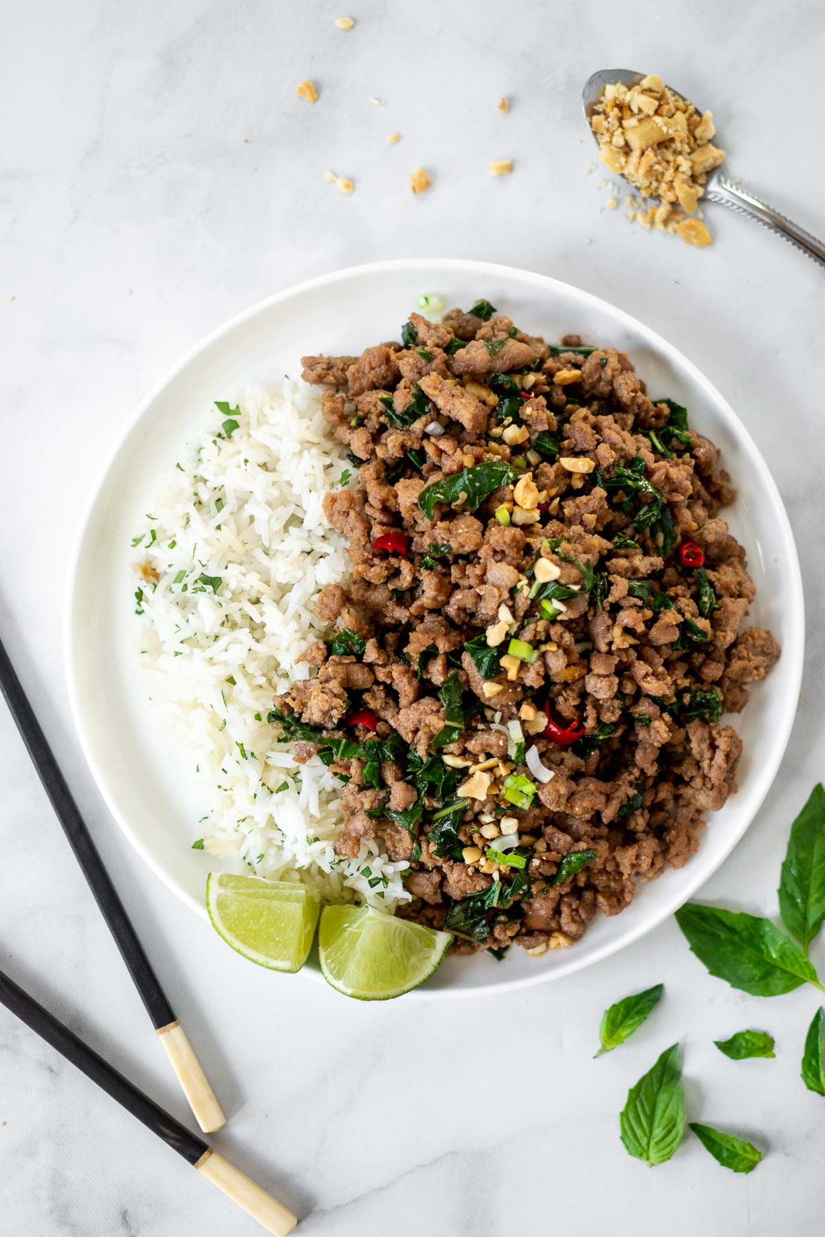 Basil pork dish on a plate with rice and peanuts.