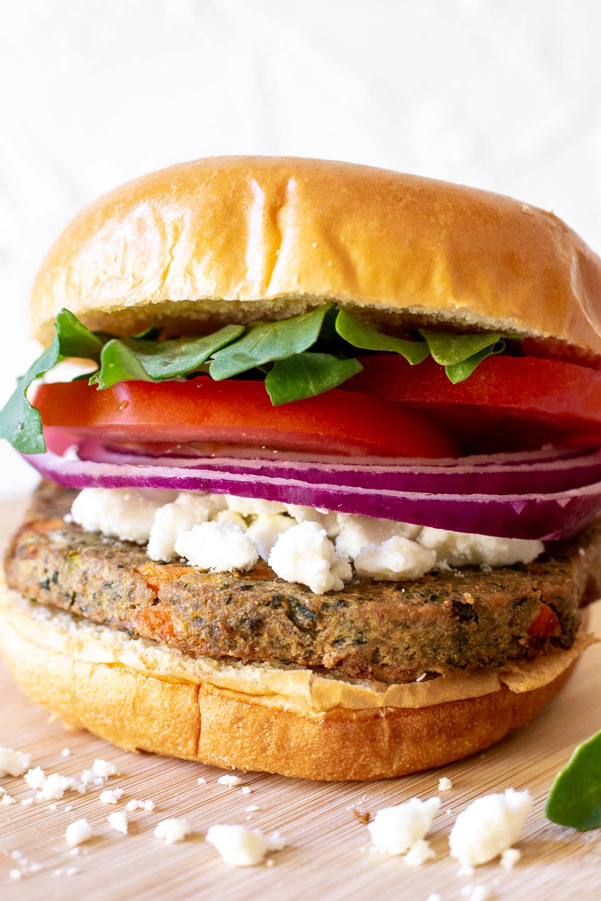 Simple veggie burger with lettuce, onions, tomatoes and feta cheese.