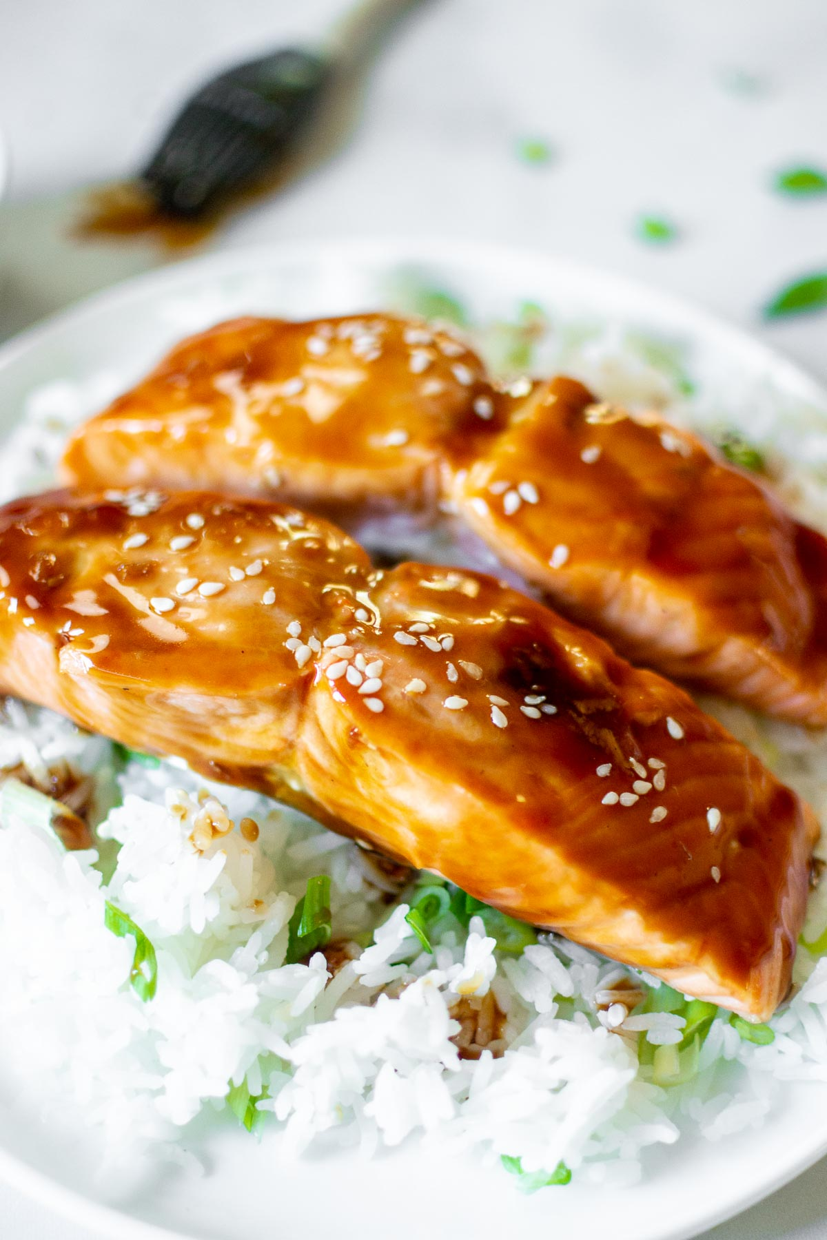 Two Teriyaki salmon filets on a plate with rice