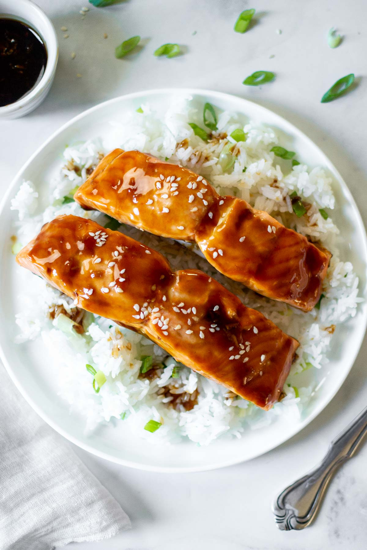 Air Fryer Teriyaki Salmon filets on a bed of rice with scallions