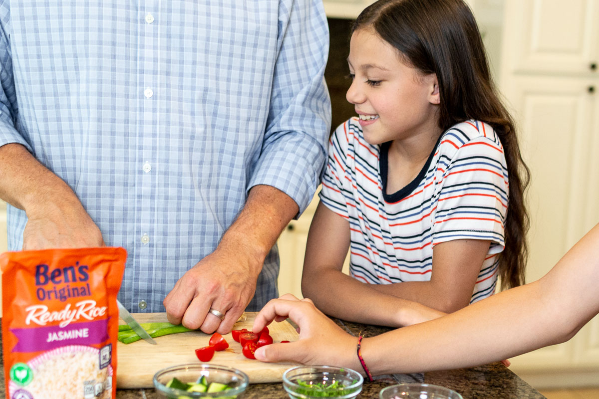 Dad cutting veggies for chicken bowls while daughter looks onl