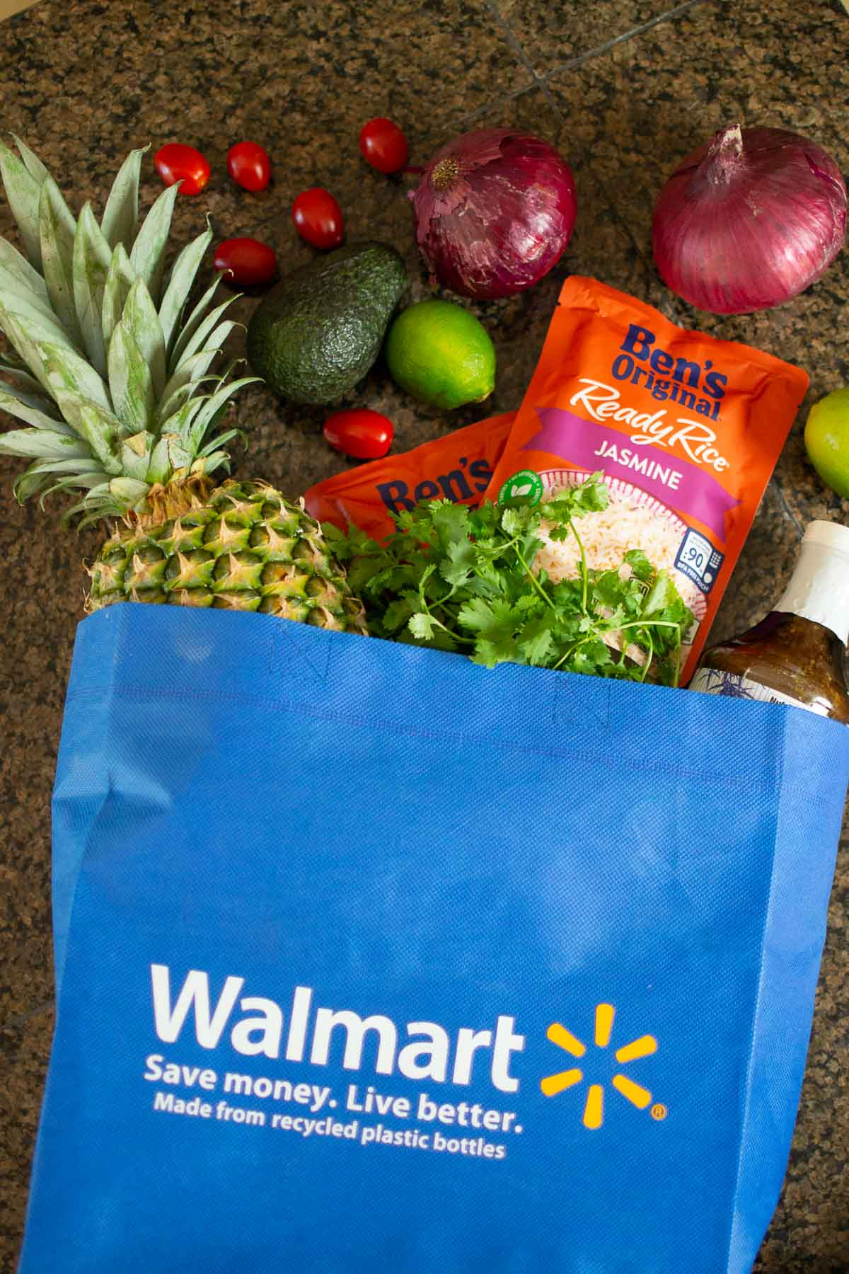 Walmart grocery bag with ingredients to make the chicken bowls spilling out of the top
