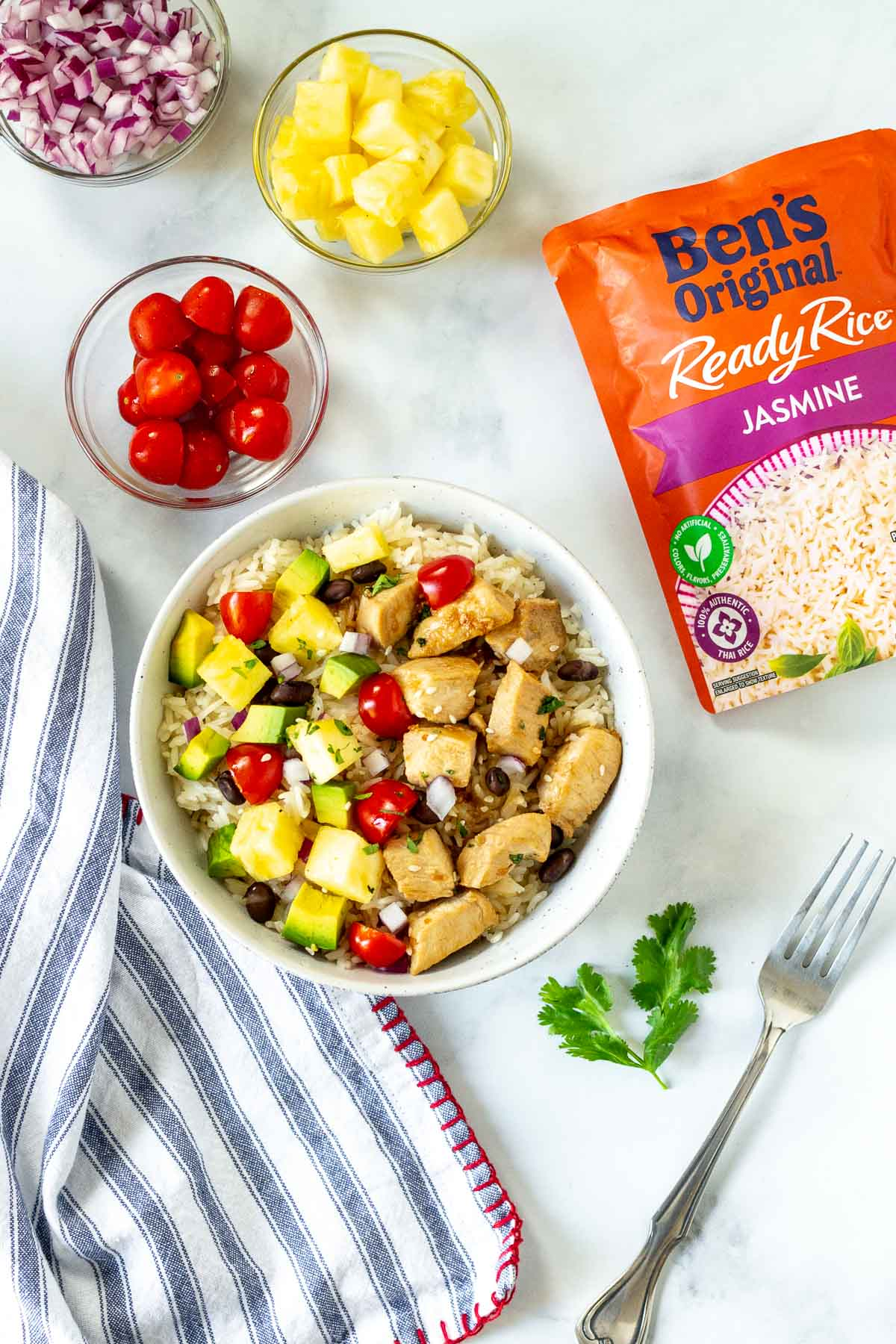 Assembled Hawaiian chicken bowl with pineapple, tomatoes and red onion in small bowls and a package of Ben's Original Jasmine rice