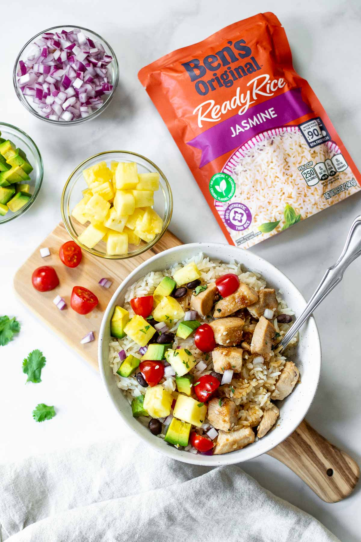 Assembled Hawaiian chicken bowl with pineapple, avocado and red onion in small bowls and a package of Ben's Original Jasmine rice