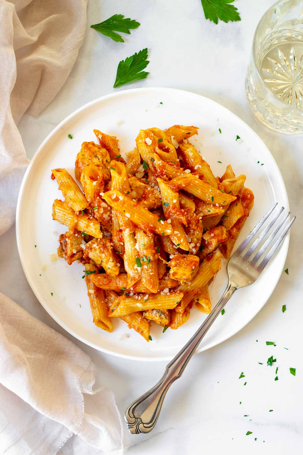 Instant Pot chicken penne on a white plate with a fork and glass of wine