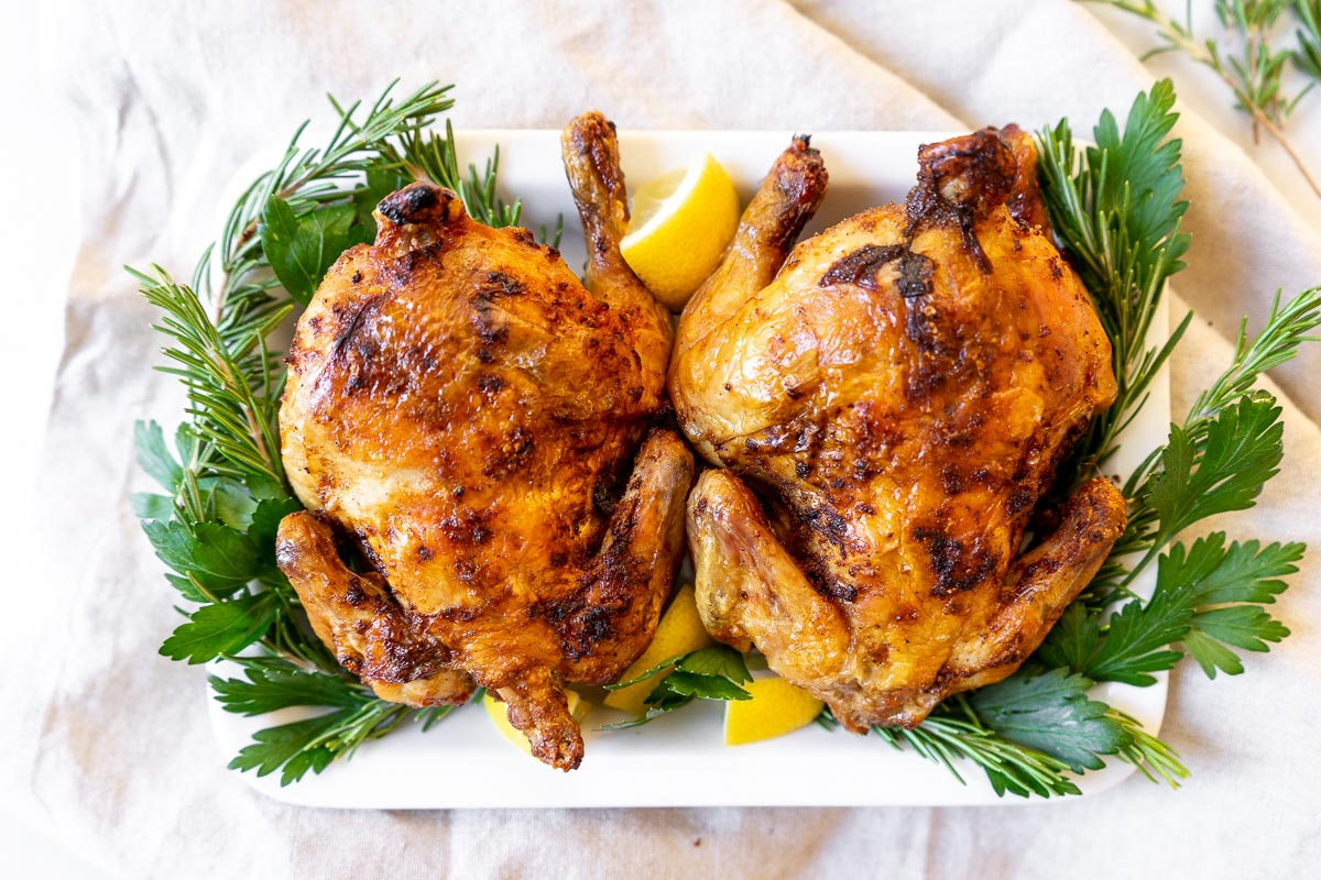 Two air fryer Cornish hens on a platter with rosemary and lemon